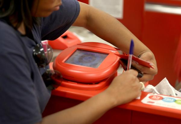A customer signs a credit card statement next to a scanner in a Target store in Miami, Florida. Target now believes that about 70 million credit and debit card accounts of customers who made purchases by swiping their cards at terminals in its U.S. stores between November 27 and December 15 may have been stolen. (Joe Raedle/Getty Images)