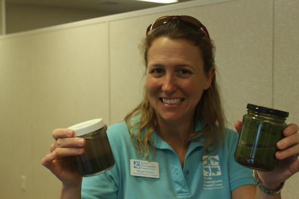 Megan Robers, spokeswoman for the Florida Oceanographic Society, displays samples of the algae gathered from the Indian River Lagoon during the summer
