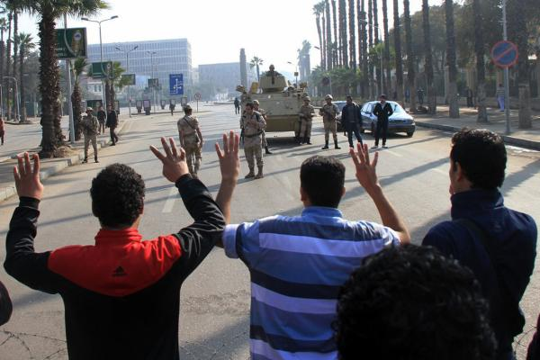 Cairo University students, who are supporters of the Muslim Brotherhood and deposed Egyptian President Mohamed Morsi, protest in front of security forces in Cairo on Jan. 10. The government has outlawed Morsi's political party and declared it a terrorist group.