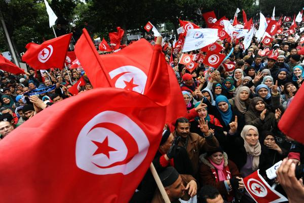 Tunisians wave their national flag and shout slogans on Tuesday in the capital, Tunis, as they attend a rally marking the third anniversary of the uprising that ousted longtime dictator Zine El Abidine Ben Ali.