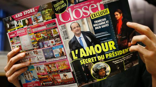 A man reads the French magazine <em>Closer</em> on Friday in Paris. The magazine said President Francois Hollande was having an affair with actress Julie Gayet.