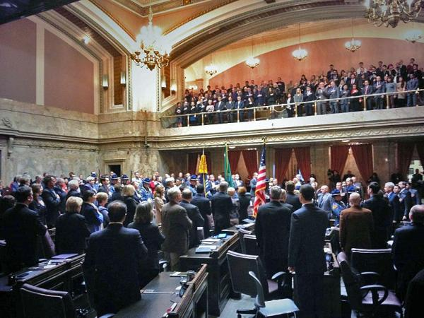 Members of the Washington legislature and guests in the gallery stand for the Washington State Patrol Honor Guard prior to Governor Jay Inslee's State of the State address.