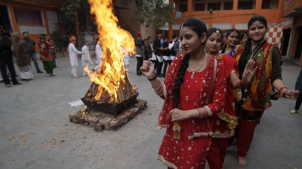 Indian women dance around a bonfire as they celebrate Lohri festival in Jammu, India, Monday. Lohri is a celebration of the winter solstice in India.