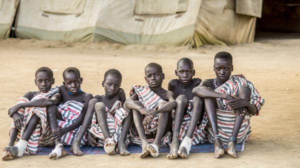 Young boys suspected of having Guinea worm infections wait for the parasite to emerge through the skin at a clinic in South Sudan.