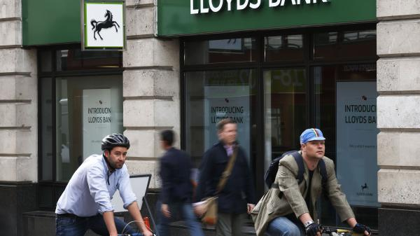 NPR's Ari Shapiro, who recently moved to London and set up a bank account, reports that it can still be an expensive and time consuming process to transfer money internationally. Here, people pass by a branch of Lloyds Bank in London, on Sept. 17.