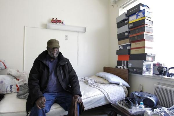 Lottery winner Malcolm Ramsey, 55, sits in his room at the Loving Care assisted living facility in St. Petersburg, Fla., with some of the shoes he bought recently with his winnings. Ramsey was on a $54 monthly allowance before buying a scratch-off ticket worth $500 a week for life. (James Borchuk/Tampa Bay Times)