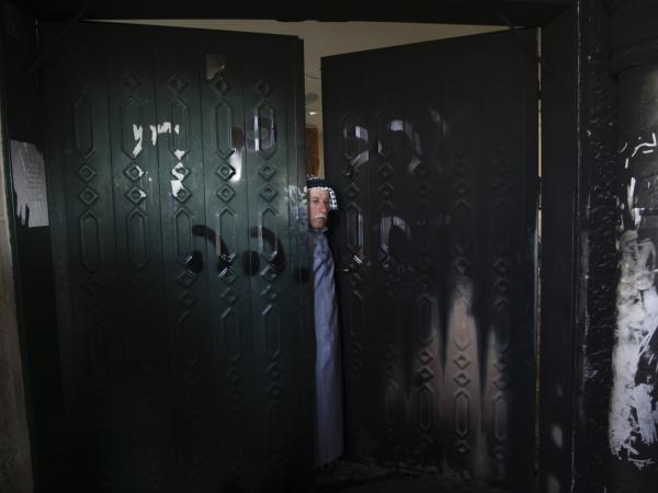 A Palestinian man stands on the doorway of a burned mosque in the West Bank village of Deir Istiya, on Wednesday.