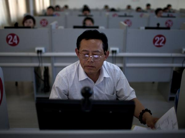 A man takes a computerized road rules test at a driving school in Jinan, in eastern China's Shandong province, in 2011. Most Chinese people — accustomed to an education system that emphasizes rote memorization — don't find the test as difficult as foreigners.
