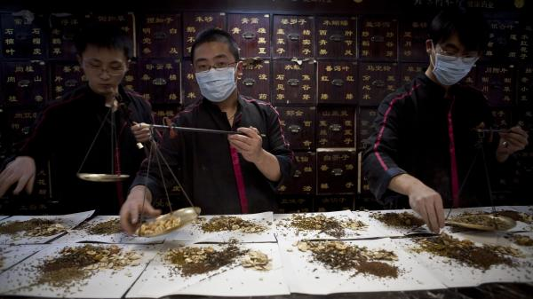 Workers prepare Chinese traditional medicine for customers in Beijing.