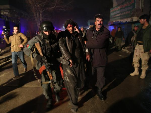 Afghanistan security forces help an injured man from the scene of the attack, where at least 21 — mostly foreigners — were killed.