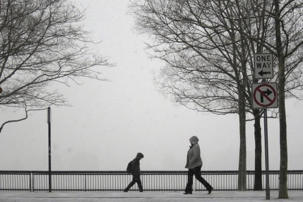 People walk in a park along the Hudson River across from New York City as snow begins to fall in Hoboken.