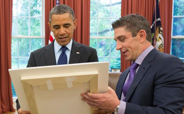 "President Barack Obama and Richard Blanco look at a framed copy of ""One Today,"" in the Oval Office, May 20, 2013. (Official White House Photo by Pete Souza)"