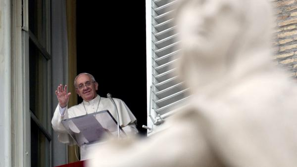 Pope Francis waves to faithful during the <em>Angelus</em> prayer from his studio overlooking St. Peter's Square at the Vatican on Sunday. President Obama will meet with the pope for the first time in March.