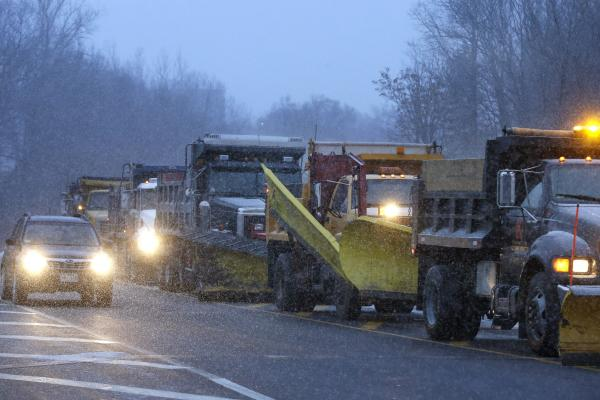 Trucks with snowplows line up on a ramp near Interstate 95, as motorists make their way around in Weston, Mass. Heavy snow has been forecast and a blizzard warning was posted for portions of Massachusetts, prompting Gov. Deval Patrick to dismiss nonemergency state workers early.