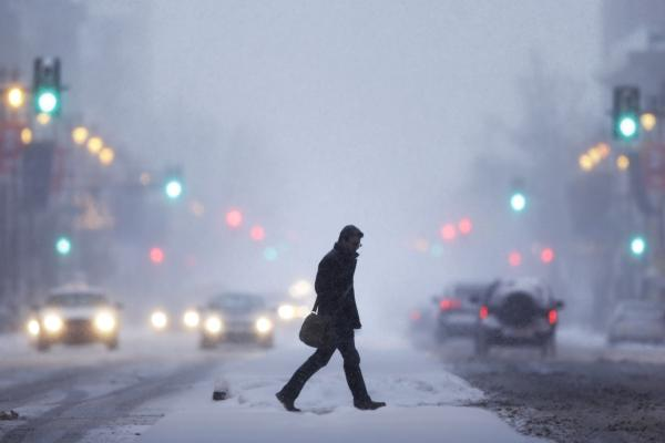 A man crosses the street Tuesday in Philadelphia. A fast-moving cold front will plunge the Northeast into a deep freeze and dump up to a foot of snow in certain regions, forecasters said.