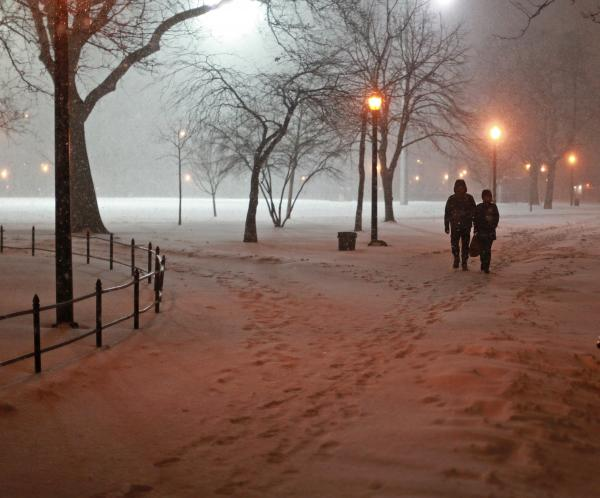 The path was snow-covered Tuesday night in Brooklyn as two people walked through a park.