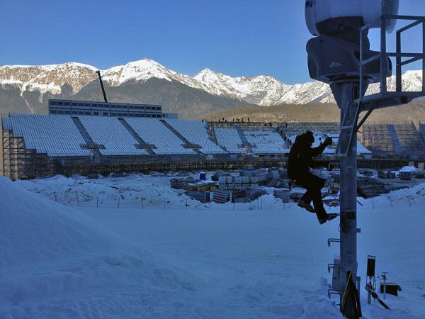 Wenatchee's Jon Wax climbs a snow making tower to perform maintenance ahead of the 2014 Sochi Olympics. In the background is the finish line for downhill ski racing at the Rosa Khutor venue.