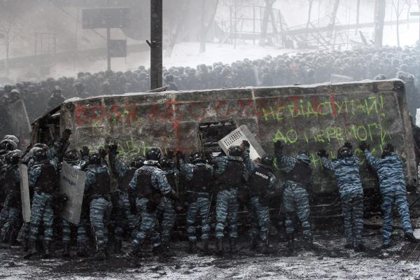 Riot police officers push a van destroyed by demonstrators.