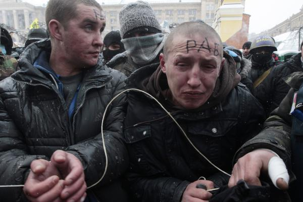 "Protesters tie up pro-government hired thugs, referred to as ""titushki,"" douse them with paint and then release them. The word ""slave"" is written on their foreheads."