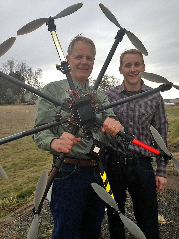 High-tech cameras, sensors, aircraft and satellites could more accurately predict crop yields and increase the cost-effectiveness of biofuels. Dan Long holds the small aircraft equipped with cameras, while John Sulik holds the controls.