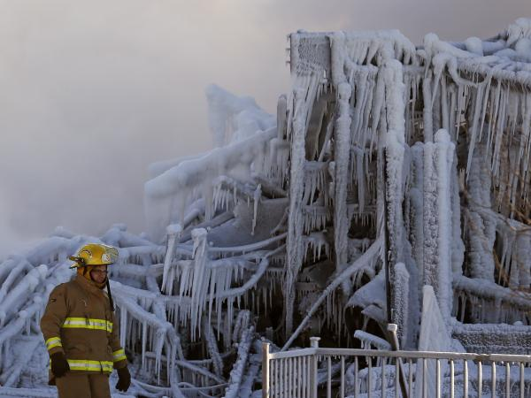 A firefighter walks past the Residence du Havre after the fire in L'Isle Verte, Quebec. At least three people died in the blaze at the seniors' home. Early reports were that another 30 people were missing.