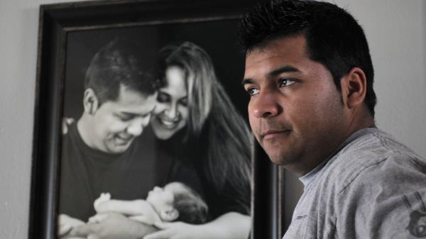 Erick Munoz stands with an undated family photograph of himself, his wife, Marlise, and their son Mateo. Erick Munoz is now fighting to have a Texas hospital remove his pregnant wife from life support, saying she is brain-dead.