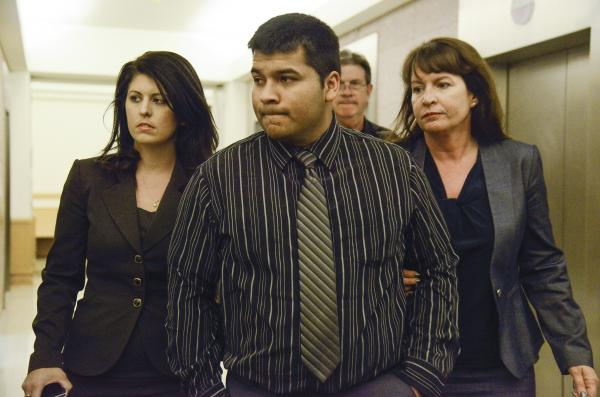 Erick Munoz is escorted by attorneys as he walks to court in Fort Worth, Texas, on Friday. A judge ordered a hospital to take Munoz's wife, who is 22 weeks pregnant, off life support.