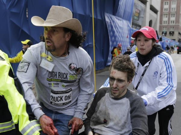 An emergency responder and volunteers, including Carlos Arredondo, in the cowboy hat, push Jeff Bauman in a wheelchair after he was injured in one of two explosions near the finish line of the Boston Marathon.