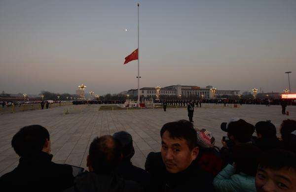 The Chinese flag is seen in front of a view of the moon at Beijing's Tiananmen Square in December, when China's first moon rover touched the lunar surface. That feat was widely celebrated — but observers believe the rover has now run into serious trouble.