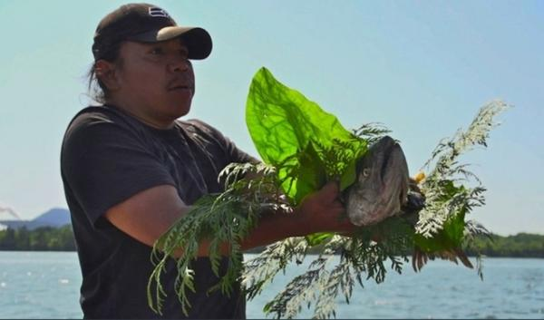 A Native American takes part in a salmon ceremony. On Tuesday, the U.S. commerce secretary declared a fishery disaster for the Fraser River sockeye salmon fishery in Washington. That could lead to aid to nine tribes and non-tribal fishers.
