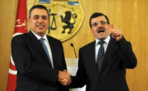 Tunisia's new Prime minister Mehdi Jomaa (left) shakes hands with his predecessor Ali Laarayedh during a handover ceremony in Tunis on January 29, 2014. (Fethi Belaid/AFP/Getty Images)