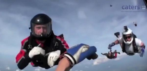 Skydivers using hand signals to coordinate a rescue of James Lee, who is unconscious.