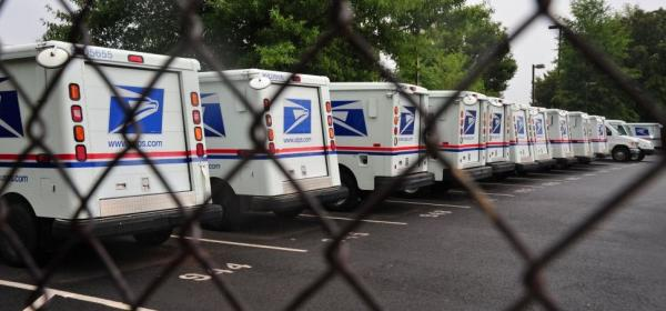 U.S. Postal Service mail delivery trucks sit idle at the Manassas post office in Virginia on September 5.