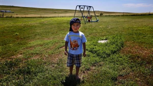 <p>Derrin Yellow Robe, 3, stands in his great-grandparents' backyard on the Crow Creek Reservation in South Dakota. Along with his twin sister and two older sisters, he was taken off the reservation by South Dakota's Department of Social Services in July 2009 and spent a year and a half in foster care before being returned to his family.</p>