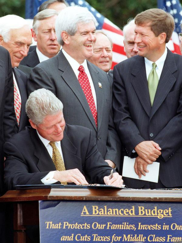 Gingrich stands with then-Republican Rep. John Kasich of Ohio while President Clinton signs the balanced-budget agreement in August 1997.
