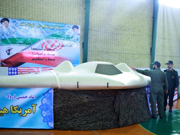 A picture released by the official website of Iran's Revolutionary Guard on Dec. 8 shows Iranian Revolutionary Guard Brig. Gen. Amir-Ali Hajizadeh (right) looking at a U.S. spy drone that crashed in Iran on Dec. 4.