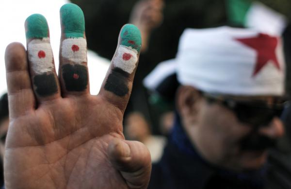 An anti-Syrian regime protester holds up his fingers painted in revolutionary flag colors during a protest outside the Arab League headquarters in Cairo, Egypt Sunday.