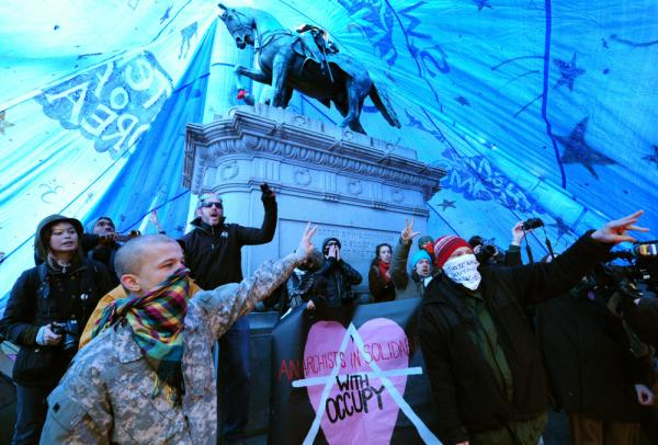 Occupy D.C. protesters shout slogans after erecting a tent over the statue of Civil War Maj. Gen. James Birdseye McPherson at McPherson Square in Washington.