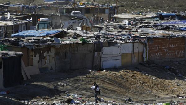 A digger demolishes a shack as a boy walks nearby in one section of the sprawling Cañada Real slum on the outskirts of Madrid on March 5. After decades of turning a blind eye to Europe's largest illegal settlement, cash-strapped authorities are demolishing homes there and taking back the land.