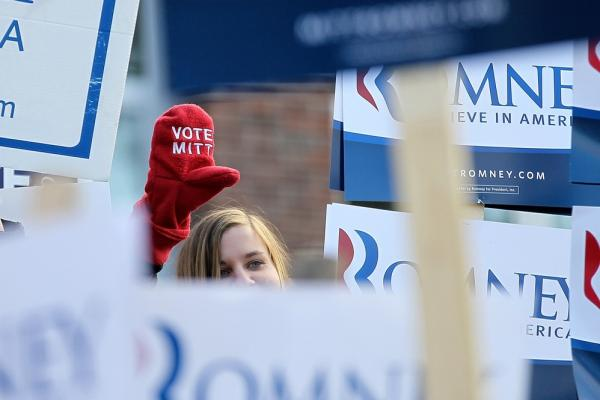 A Mitt Romney supporter stands outside the Webster School polling station in Manchester.