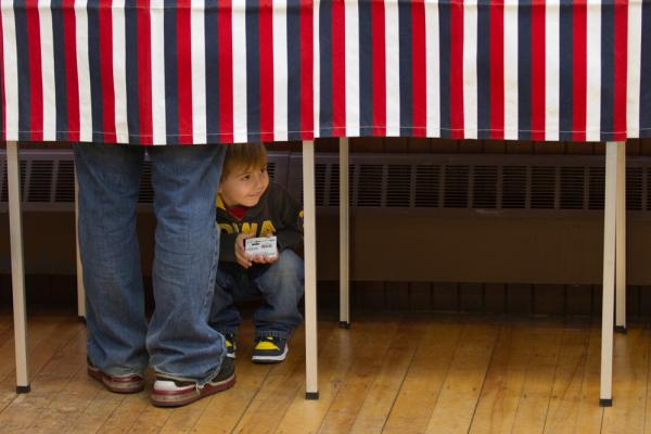 Cameron Carbone, 4, peeks out of the voting booth as his father votes in Wilton.