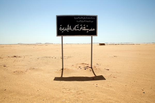 "A sign on undeveloped land welcomes visitors to ""New Toshka City."" Toshka was to be a new settlement along the Upper Nile Valley, complete with enough jobs and infrastructure to support the relocation of 20 million Egyptians from polluted and over-crowded cities."