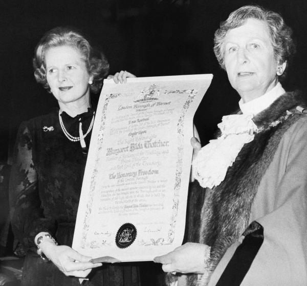 Prime Minister Thatcher (left) shows off her scroll after receiving an honor from the London Borough of Barnet at Barnet Town Hall, Feb. 6, 1980. With Thatcher is the mayor of Barnet, Councilor Rita Levy.