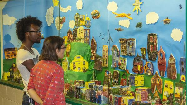 Checking out a wall display of art from the Claymobile.