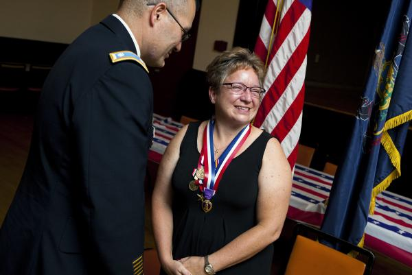 Retired Army Maj. Michelle Dyarman, shown with Lt. Col. William McDonough, smiles after receiving a Purple Heart and other medals for her military service.
