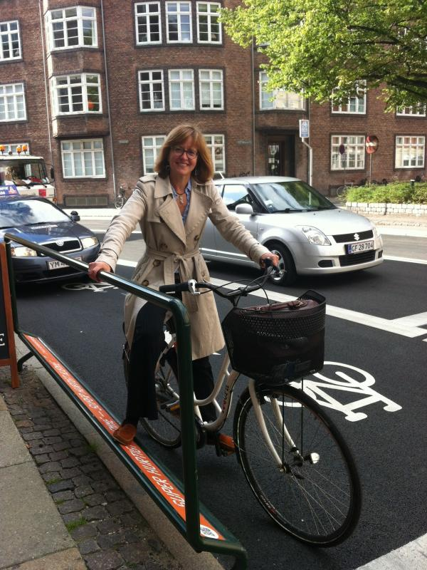 NPR reporter Eleanor Beardsley rides in one of the new bike lanes in Copenhagen. The city is building more than two dozen lanes from the suburbs into the city. They cater to cyclists by including such things as rails and footrests at stoplights.