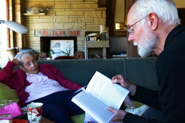 Margaret Zerwekh, who has lived in the mill house for half a century, listens to Milton Bates read from his book, <em>Bark River Chronicle</em>s. Zerwekh's home is a treasure trove of Delafield history.
