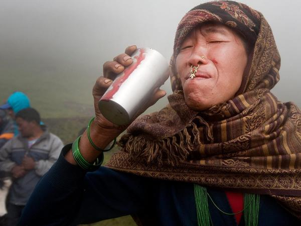A woman drinks a glass of fresh yak blood. She is attending the festival with her family in hopes that drinking the blood will help heal her ongoing digestive problems. Some people go for the day; others stay the entire week. The average attendee drinks a glass of blood per day.