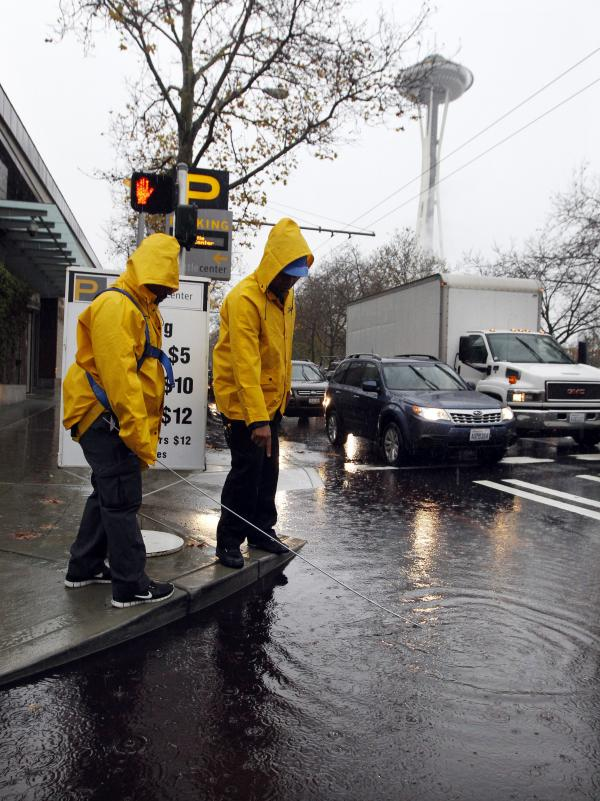 Parking attendants search for a clogged drain in Seattle Monday. Pacific storms are rolling across the Northwest, according to the National Weather Service.