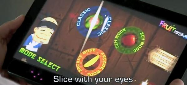 In an image from an Eye Tribe video, a man uses his eyes to play the Fruit Ninja game, slicing fruit in half as it appears on the screen.